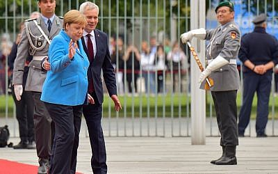 German Chancellor Angela Merkel and Finland's Prime Minister Antti Rinne (3rdL) walk after listening to the national anthems during a welcoming ceremony with military honours at the Chancellery in Berlin on July 10, 2019. (Tobias SCHWARZ / AFP)