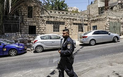 An Israeli policeman walks outside the former house of the Palestinian Siyam family during their eviction in the East Jerusalem neighborhood of Silwan on July 10, 2019. (Ahmad Gharabli/AFP)