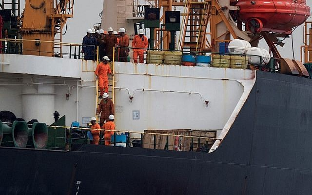 In this photo from July 6, 2019, crew members walk down a ladder on board supertanker Grace 1, off the coast of Gibraltar on July 6, 2019. (Jorge Guerrero/AFP)