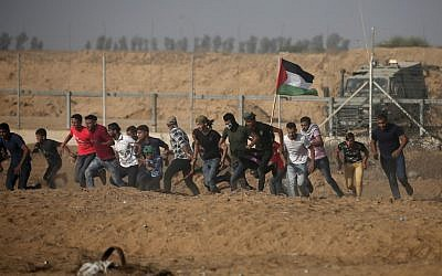 Palestinian demonstrators run away from the fence during protests along the border with Israel, east of Khan Yunis, in the southern Gaza Strip on July 12, 2019. (Mahmud Hams/AFP)