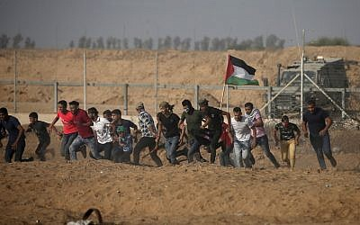 Palestinian demonstrators run away from the fence during protests along the border with Israel, east of Khan Younis, in the southern Gaza Strip on July 12, 2019. (Mahmud Hams/AFP)