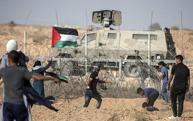 Palestinian demonstrators throw stones at Israeli security forces during protests along the border with Israel, east of Khan Younis, in the southern Gaza Strip on July 12, 2019. (MAHMUD HAMS / AFP)
