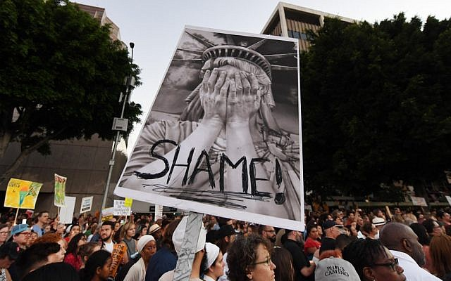 People protest against the upcoming ICE raids and detentions of refugee asylum seekers at a vigil outside the main ICE detention center (background) in downtown Los Angeles on July 12, 2019. (Mark RALSTON / AFP)