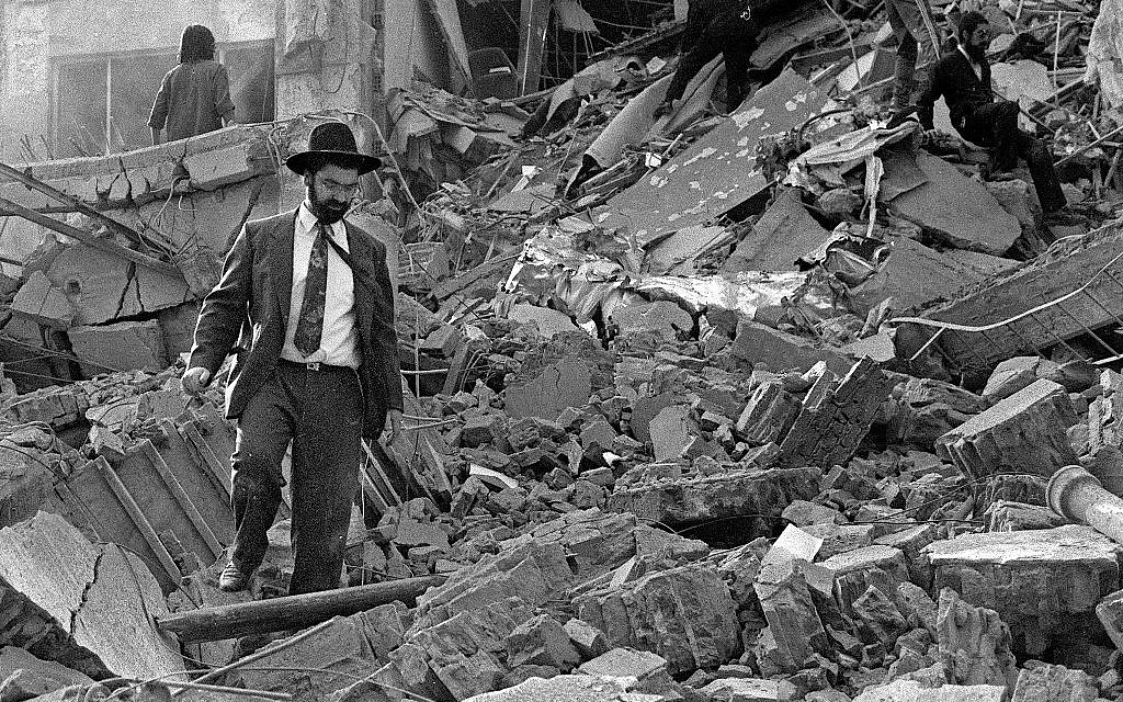 In this photo from July 18, 1994, a man walks over the rubble left after of the Argentinian Israeli Mutual Association (AMIA)  building in Buenos Aires after it was targeted in a deadly bombing. (Ali Burafi/AFP)