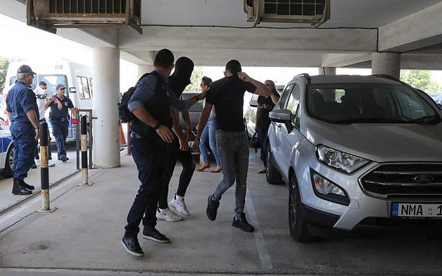 Twelve Israeli tourists, suspected of raping a 19-year-old British girl in Ayia Napa, arrive at the court premises in the eastern Cypriot resort of Paralimni on July 18, 2019, for a remand hearing conducted behind closed doors. (AFP)