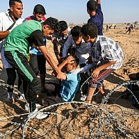 Illustrative: Palestinian protesters assist an injured protester during clashes with Israeli forces across the barbed-wire fence during a border demonstration near Rafah in the southern Gaza Strip on July 19, 2019. (SAID KHATIB / AFP)