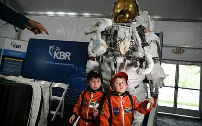 Young attendees stand by a space suit during the Apollo 11, 50th anniversary celebration at Space Center Houston on July 20, 2019, in Houston, Texas. (Loren ELLIOTT / AFP)