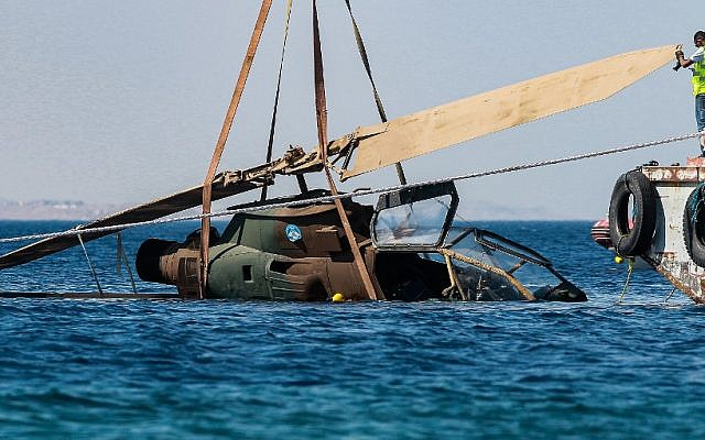 This picture taken on July 24, 2019 shows a decommissioned Jordanian Armed Forces' AH-1 Cobra helicopter being submerged into the waters of the Red Sea off the coast of the southern Jordanian port city of Aqaba, as part of preparations for a new underwater military museum. (Khalil MAZRAAWI / AFP)