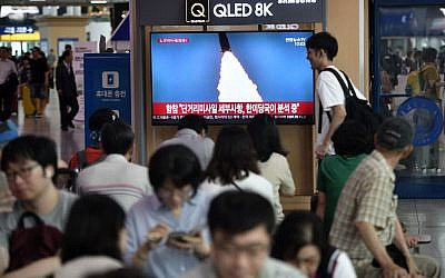 People watch a television news screen showing a file footage of a North Korean missile launch, at a railway station in Seoul on July 25, 2019. (Jung Yeon-je / AFP)