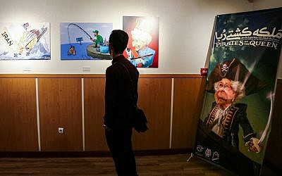 A man views caricatures at the 'Pirates of the Queen' cartoon exhibition showing artwork by Iranian artists portraying Britain's Queen Elizabeth II as a pirate over the seizure of an Iranian oil tanker earlier in the month, at the Osveh Art and Cultural Center in the capital Tehran on July 30, 2019. (Atta Kenare/AFP)