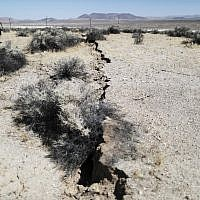 An onlooker views newly ruptured ground after a 7.1 magnitude earthquake struck in the area on July 6, 2019 near Ridgecrest, California. (Mario Tama/Getty Images/AFP)