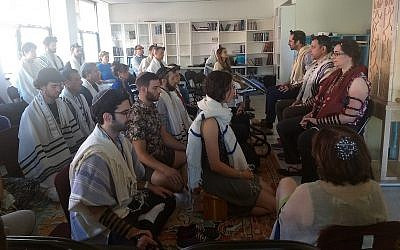 Illustrative: Students meditate as part of the morning prayer at Romemu Yeshiva in New York, July 16, 2019. The yeshiva combines intensive study of Jewish text with mindfulness and mysticism. (Ben Sales)