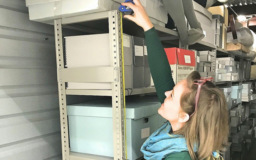 Museum of the Southern Jewish Experience project coordinator, Anna Tucker, measures shelves used to store artifacts ahead of the move last month. (Courtesy of the Museum of the Southern Jewish Experience)