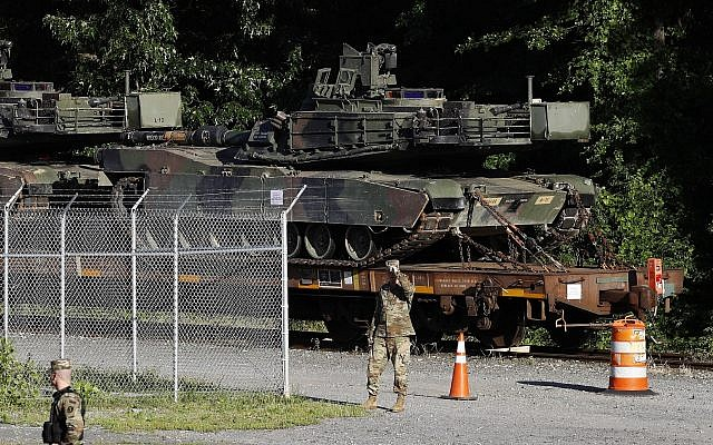 Military police walk near Abrams tanks on a flat car in a rail yard, July 1, 2019, in Washington, ahead of a Fourth of July celebration that US President Donald Trump says will include military hardware. (AP Photo/Patrick Semansky)