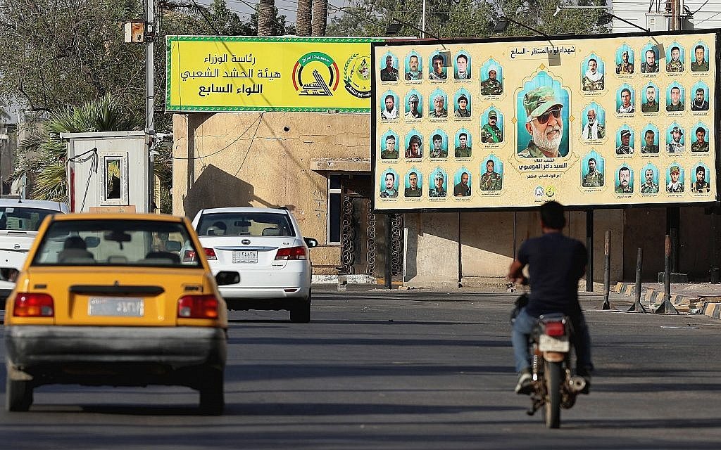 In this July 2, 2019 photo, motorists pass by a Popular Mobilization poster of volunteer militants who were killed in Iraq fighting Islamic State militants in Basra, Iraq. (AP Photo/Nabil al-Jurani)