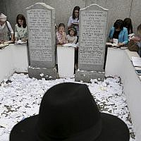 In this photo from July 2, 2019, people pray at the gravesite of Rabbi Menachem M. Schneerson in the Queens borough of New York. (AP Photo/Seth Wenig)
