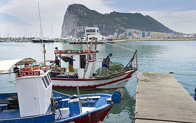 In this file photo taken on May 28, 2012, Spanish fishing boats sit moored in La Linea de Concepcion, Spain, backdropped by the Rock of Gibraltar.  (AP Photo/Marcos Moreno, File)
