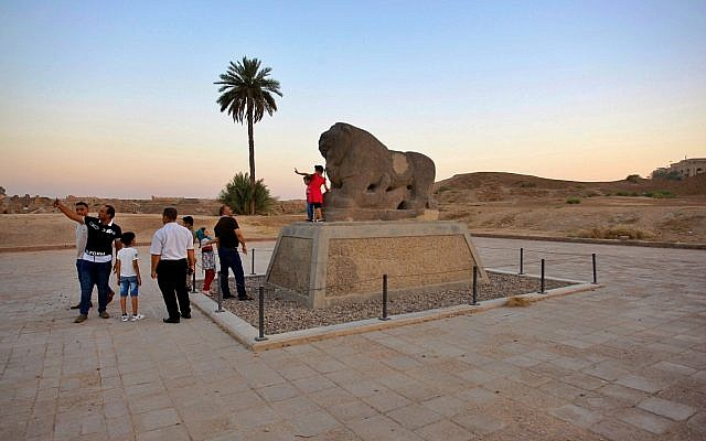 People stand near the Lion of Babylon at the archaeological site of Babylon, Iraq, Friday, July 5, 2019.. (AP Photo/Anmar Khalil)