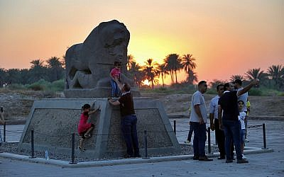People stand near the Lion of Babylon at the archaeological site of Babylon, Iraq, Friday, July 5, 2019.(AP Photo/Anmar Khalil)