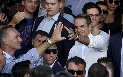 Greek opposition New Democracy conservative party leader Kyriakos Mitsotakis waves his supporters after casts his ballot at a polling station in Athens, on Sunday, July 7, 2019.  (AP Photo/Petros Giannakouris)