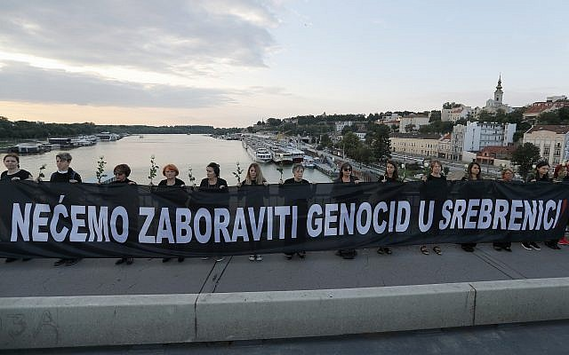 "Members of the anti-war organization ""Women in Black"" hold a banner that reads: ""We will not forget the genocide in Srebrenica!'' as part of a meeting to mark the 24th anniversary of the Srebrenica tragedy, in Belgrade, Serbia, July 10, 2019. (AP Photo/Darko Vojinovic)"