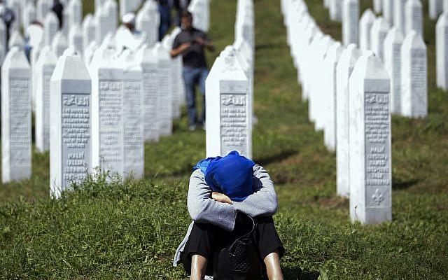 A woman rests at the memorial cemetery, prior to the funeral, in Potocari, near Srebrenica, Bosnia, July 11, 2019. (AP Photo/Darko Bandic)