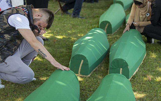 Mourners pray next to coffins in Potocari near Srebrenica, Bosnia, July 11, 2019. The remains of 33 victims of the Srebrenica massacre are buried 24 years after Serb troops overran the eastern Bosnian Muslim enclave of Srebrenica and executed some 8,000 Muslim men and boys, an event international courts have labeled as an act of genocide. (AP Photo/Darko Bandic)