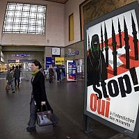 People walk by a poster from the right-wing Swiss People's Party (SVP/UDC) depicting a woman wearing a burqa in front of a Swiss flag upon which are minarets which resemble missiles, at the central station in Geneva, Switzerland, November 4, 2009. (Salvatore Di Nolfi/Keystone/AP)