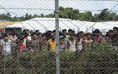 Rohingya refugees gather near a fence during a government organized media tour to a no-man's land between Myanmar and Bangladesh, near Taungpyolatyar village, Maung Daw, northern Rakhine State, Myanmar, June 29, 2018. (Min Kyi Thein/AP)