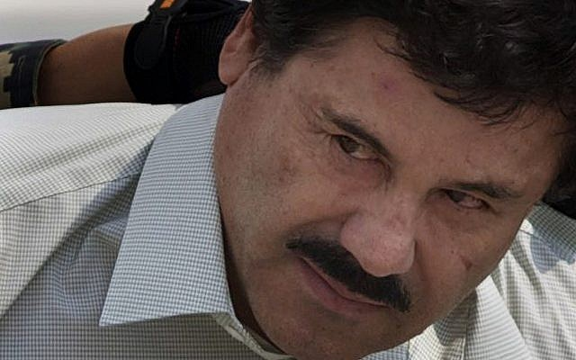 In this February 22, 2014, file photo, Joaquin 'El Chapo' Guzman is escorted to a helicopter in handcuffs by Mexican navy marines at a navy hanger in Mexico City. (AP Photo/Eduardo Verdugo, File)