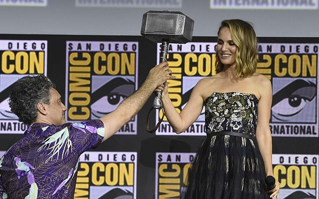 "Director Taika Waititi hands the Thor hammer to Natalie Portman during the ""Thor Love And Thunder"" portion of the Marvel Studios panel on day three of Comic-Con International on July 20, 2019, in San Diego. (Chris Pizzello/Invision/AP)"