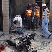 Pakistani security officials and rescue workers gather at the site of a suicide bombing at an entrance to a hospital in Dera Ismail Khan, Pakistan, July 21, 2019. (AP Photo/Ishtiaq Mahsud)