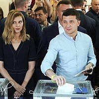 Ukrainian President Volodymyr Zelenskiy, right, and his wife Olena Zelenska cast their ballots at a polling station during a parliamentary election in Kiev, Ukraine on July 21, 2019. (AP/Evgeniy Maloletka)