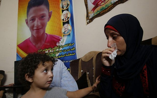 Raeda, mother of 14-year-old Mohammed Ayyoub, sits near a poster with his photo, at the family home in Jabaliya refugee camp, July 2, 2019. Mohammed was killed during a protest on the fence separating Israel and Gaza in 2018. (AP Photo/Hatem Moussa)