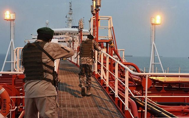 In this Sunday, July 21, 2019 photo, two armed members of Iran's Revolutionary Guard inspect the British-flagged oil tanker Stena Impero, which was seized in the Strait of Hormuz on Friday by the Guard, in the Iranian port of Bandar Abbas (Morteza Akhoondi/Mehr News Agency via AP)
