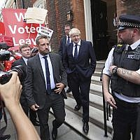 Conservative Party leadership contender Boris Johnson, center right, leaves his office in the Westminster area of London, July 22, 2019. (Yui Mok/PA via AP)