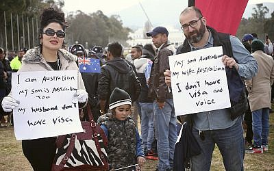 Lida Aftahi, left, her husband Heydar Aftahi, right, and their 4-year-old son, Ramssin, take part in a refugee protest at Parliament House in Canberra, Australia, July 29, 2019. (AP Photo/Rod McGuirk)