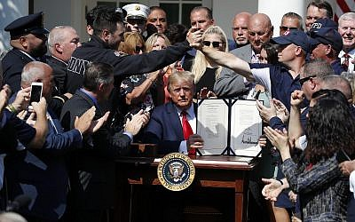US President Donald Trump holds up the signed H.R. 1327 bill in the Rose Garden of the White House on July 29, 2019, in Washington. (AP/Alex Brandon)