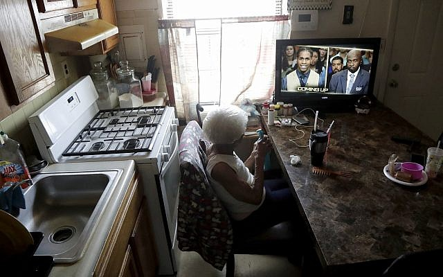 Carrie Newson watches television in the dining area inside her home at the Dutch Village apartments, in Baltimore, July 30, 2019. (Julio Cortez/AP)