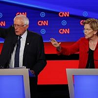 Senator Bernie Sanders (Independent-Vermont) and Senator Elizabeth Warren (Democrat-Massachusetts) talk during in the first of two Democratic presidential primary debates hosted by CNN July 30, 2019, in the Fox Theatre in Detroit. (AP Photo/Paul Sancya)