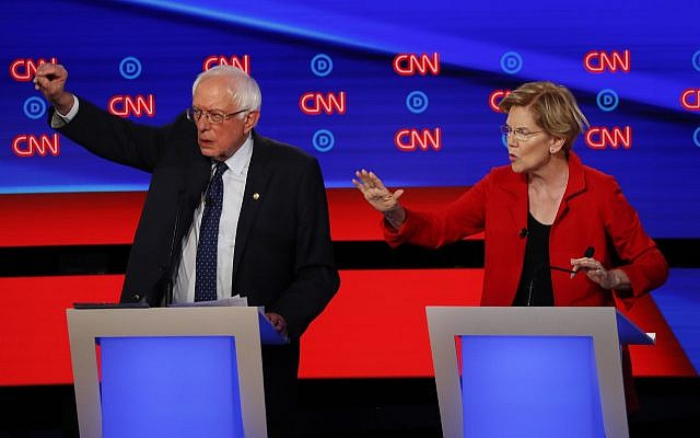 Illustrative: Senator Bernie Sanders (Independent-Vermont) and Senator Elizabeth Warren (Democrat-Massachusetts) talk during in the first of two Democratic presidential primary debates hosted by CNN July 30, 2019, in the Fox Theatre in Detroit. (AP Photo/Paul Sancya)