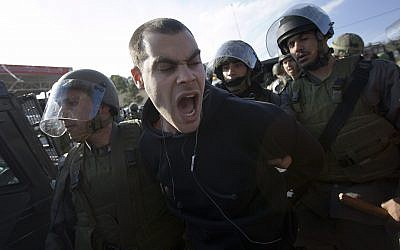 Left-wing activist Jonathan Pollak is detained by Israeli soldiers during a protest over a disputed water well in the West Bank village of Nabi Saleh near Ramallah, January 22, 2010. (AP Photo/Bernat Armangue)