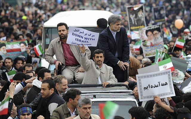 Escorted by his bodyguards, Iranian President Mahmoud Ahmadinejad, holds an anti-Israel placard, from his car, as he attends a rally marking the 32nd anniversary of the 1979 Islamic Revolution, at the Azadi (Freedom) Square in Tehran, Iran, Friday, Feb. 11, 2011. (AP Photo/Vahid Salemi)