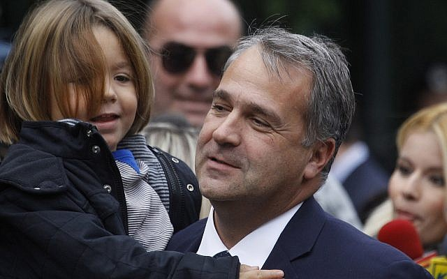 New Transport and Infrastructure Minister Makis Voridis, member of the right-wing party LAOS, arrives at the Presidential Palace holding his son in Athens on November 11, 2011. (Dimitri Messini/AP)