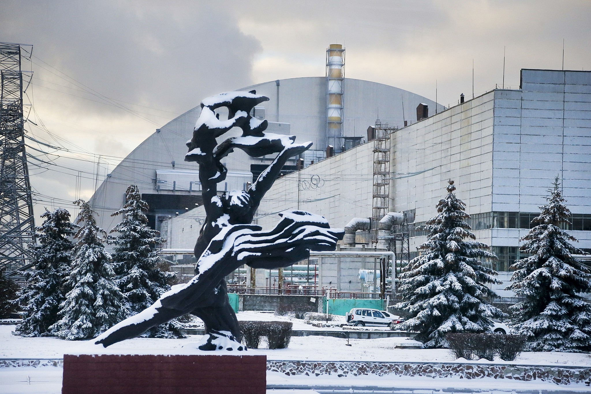 """A monument to the victims of the Chernobyl tragedy in front of the """"safe confinement shelter"""" installed over the exploded reactor at the Chernobyl nuclear plant, Chernobyl, Ukraine, Nov. 29, 2016. The newly completed shelter was one of the most ambitious engineering projects in the world. (AP Photo/Efrem Lukatsky)"""