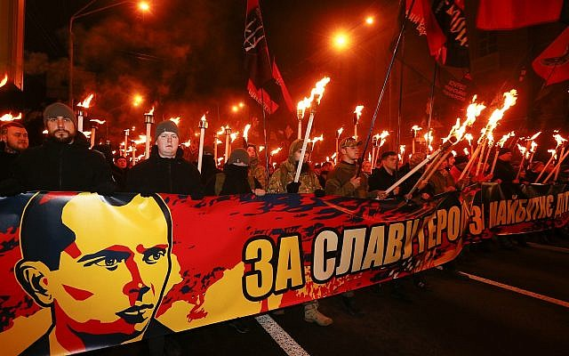 Activists of various nationalist parties carry torches during a rally in Kiev, Ukraine, January 1, 2018, behind a banner showing Nazi collaborator Stepan Bander.  (AP/Efrem Lukatsky)