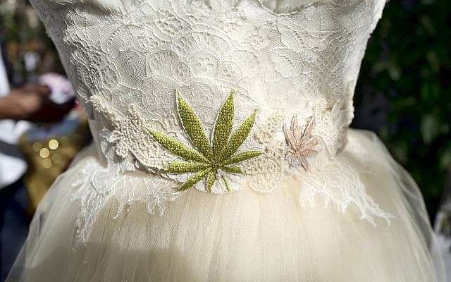 A wedding dress with an embroidered marijuana leaf on the front was displayed at the High Vibe Bride booth during the Cannabis Wedding Expo in Los Angeles in January 2019 (AP Photo/Richard Vogel)