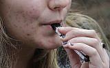 A high school student uses a vaping device near a school campus in Cambridge, Massachusetts, April 11, 2018. (AP Photo/Steven Senne, File)
