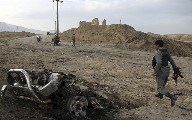 Illustrative: Afghan security forces gather at the site of an attack near the Bagram Air Base, north of Kabul, Afghanistan, April 9, 2019. (Rahmat Gul/AP)