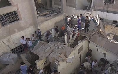 In this frame grab from from video, people search in the rubble following Saudi-led coalition airstrikes that killed at least six, including children, officials said, in the residential center of the capital, Sanaa, Yemen, May 16, 2019. (AP Photo)